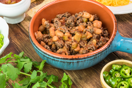 pinto beans: Close up of bowl with mixed beef and pinto beans, chili pepper -  ingredients for nachos on a wooden background. Stock Photo