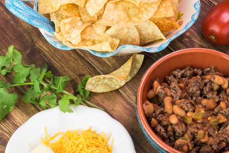 pinto beans: Close up of bowl with mixed beef and pinto beans, tortilla chips - ingredients for nachos on a wooden background. Stock Photo