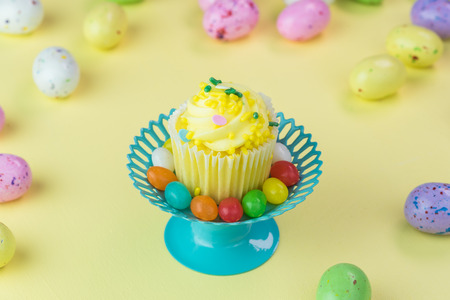 cup cakes: Close up of cupcake stand with easter cupcake  and chocolate candy eggs on pastel background. Stock Photo