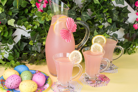 Close up of pitcher, decorated  paper butterfly, and glasses with pink lemonade, easter eggs on party table.