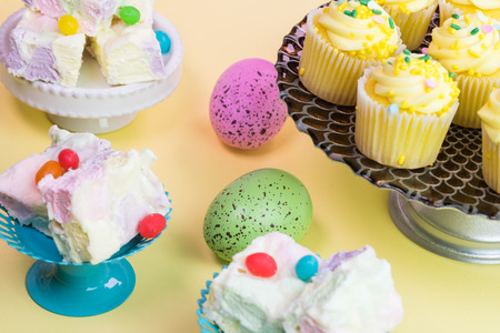 fruity: Close up of fruity marshmallow squares and cake platter with easter cupcakes, eggs on pastel background. Stock Photo