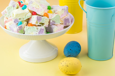fruity: Close up of cake platter with homemade fruity marshmallow squares and easter eggs on a table.