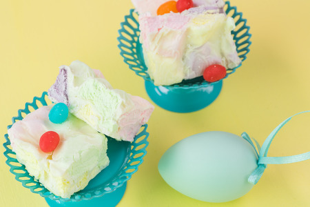 fruity: Close up of cupcake stands with homemade fruity marshmallow squares and egg on pastel wooden background.