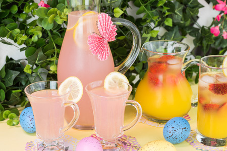paper punch: Close up of pitcher, decorated  paper butterfly, and glasses with pink lemonade and pitcher with strawberry orange blossom punch on party table.