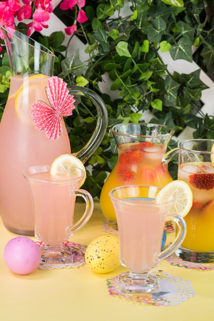 orange blossom: Close up of pitcher, decorated  paper butterfly, and glasses with pink lemonade and pitcher with strawberry orange blossom punch on party table.