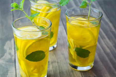 Close up of of glasses with ginger, fresh mint, lemons infused turmeric water on wooden background. Stock Photo