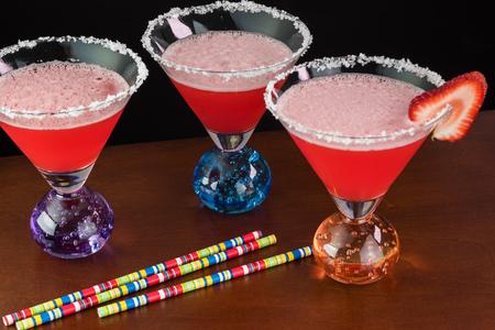 cocteles de frutas: Primer plano de gafas con un cóctel de fresa margarita con guarnición de borde de sal y las fresas en una mesa. Foto de archivo