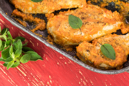 Close up of skillet with chicken breast in chili sauce on a red wooden blackground.