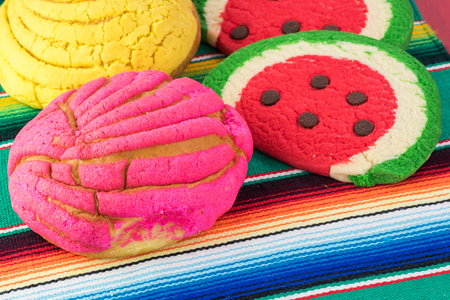 Close up of mexican butter cookies and colorful powdered sugar bread on tradition mexican table runner.