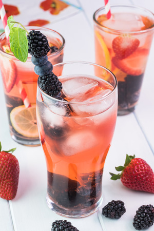 Close up of glasses of berries citrus, mint infused water with ice on a wooden background. Stock Photo