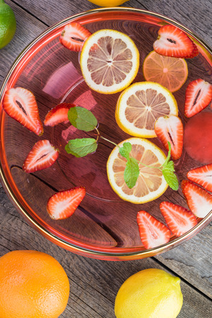 Close up of glass bowl with strawberry, citrus, mint infused water on wooden background.