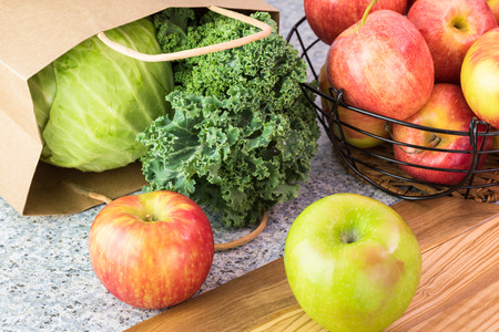 Close up of kitchen table with ripe apples, kale and green cabbage from farmers market.