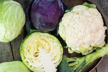 head of cauliflower: Close up of purple cabbage. cauliflower and green cabbage in a farmers tables.