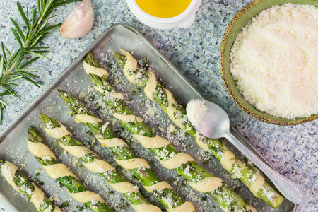 Close up of wrapped asparagus on a baking tray and ingredients  - rosemary, oil, grated parmesan cheese on the kitchen table. Reklamní fotografie