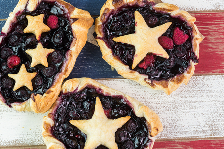 forth: Close up of  fresh homemade pies for Forth of July celebration on wooden background.