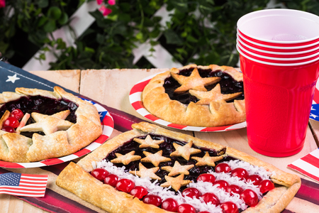 forth: Close up of decorated patio table  for Forth of July celebration with homemade blueberry pies.