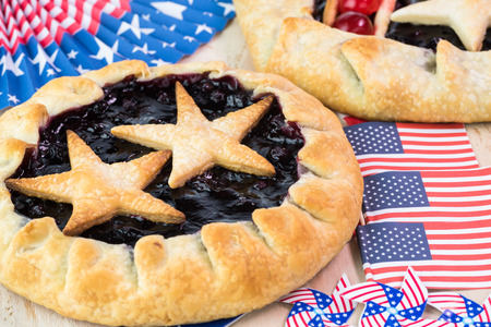 forth: Close up of  fresh homemade pies for Forth of July celebration on decorated wooden background.