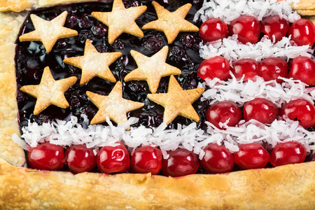 forth: Close up of  fresh homemade blueberry pie, decorated with stars, cherry and coconut flakes for Forth of July celebration.