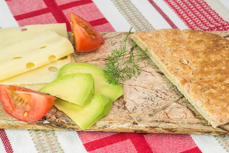 cutting bord: Close up of fresh ingredients for pita pocket sandwich. Slices of cheese, avocado, tomato on a cutting bord.