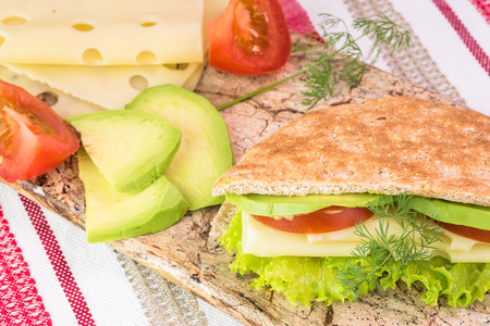 multi grain sandwich: Close up of fresh pita pocket sandwich with cheese, avocado, tomato and lettuce on a cutting board.