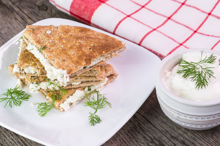 cf: Close up cf plate with stack of toasted and cut feta stuffed pita pocket with dill and small bowl with sour cream on a wooden backgroumd. Stock Photo