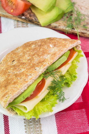 multi grain sandwich: Close up of fresh pita pocket sandwich with cheese, avocado, tomato and lettuce on a white plate. Stock Photo