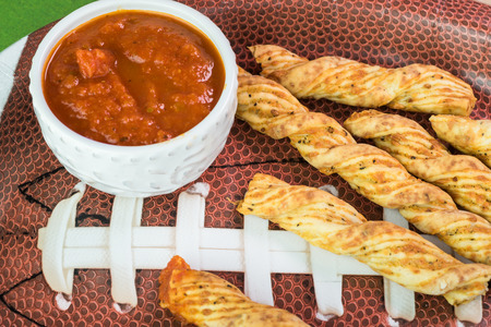 Close up of football shaped plate with garlic cheese breadsticks on the table decotated for football game party.