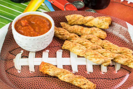 decotated: Close up of football shaped plate with garlic cheese breadsticks on the table decotated for football game party.