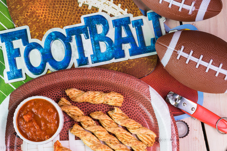 decotated: Top of view of football shaped plate with garlic cheese breadsticks on the table decotated for football game party.