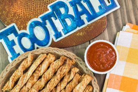 marinara sauce: Close up of garlic cheese breadsticks and bowl of marinara sauce on a football game decoration party table. Stock Photo
