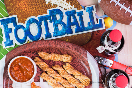 decotated: Top of view of plate with garlic cheese breadsticks and bottles of beer on the table decotated for football game party.