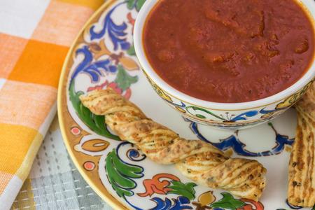 marinara sauce: Close up of garlic cheese breadsticks and bowl of marinara sauce on a table