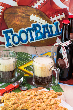 decotated: Close up of glasses of beer and tray with garlic cheese breadsticks on the table decotated for football game party.