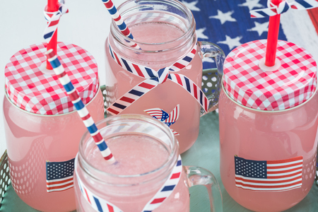 forth: Close up of pink lemonade mugs decorated for Forth of July celebration on a metal  tray.