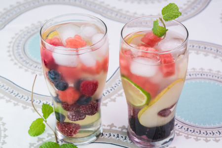 Close up of two glasses with berries and fruit, mint  infused water with ice.
