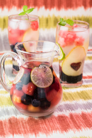 Close up of pitcher with berries and fruit, mint  infused cold water . Imagens