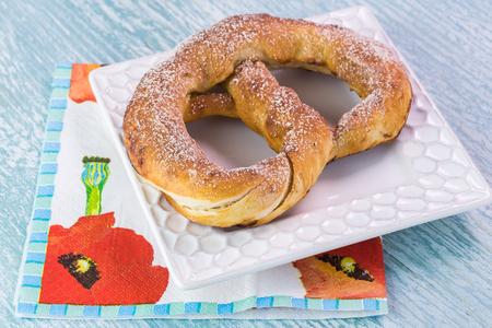 Close up of fresh baked soft cinnamon flavored pretzel on a wooden background. Banco de Imagens
