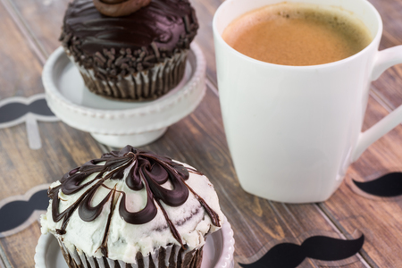 topper: Close up of chocolate cupcake with mustache cupcake topper and cup of coffee.