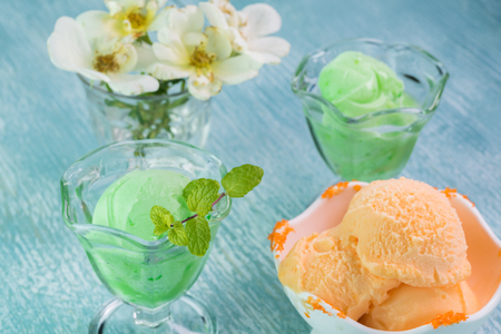 sherbet: Close up of ice cream bowls with lime and orange sherbet on a blue wooden background. Stock Photo