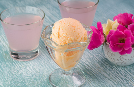 sherbet: Close up of glass bowl with orange sherbet and glasses of pink lemonade on a blue wooden background.