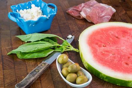 Close up of ingredients for watermelon pizza. Crumbled feta cheese, olives, prosciutto and slice of watermelon. Фото со стока