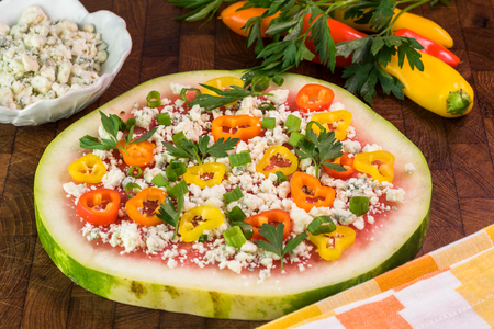 Close up of watermelon pizza with crumbled blue cheese,  bell peppers, green onion, parsley on a cutting board.