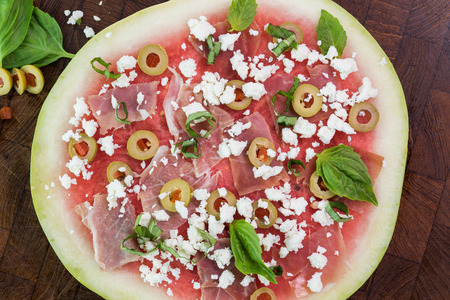 Close up of watermelon pizza with crumbled feta cheese, prosciutto, basil leafs and olives on a cutting board.