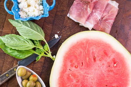 crumbled: Close up of ingredients for watermelon pizza. Crumbled feta cheese, olives, prosciutto and slice of watermelon. Stock Photo