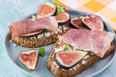 Close up of homemade bruschetta with blue crumbled cheese, prosciutto and sliced fresh figs on blue plate.