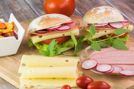 Close up of cutting board with ingredients for ham cheese sandwiches with vegetables. Banco de Imagens