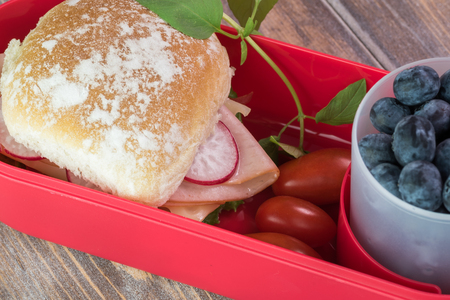 bento box: Close up of bento box with ham cheese sandwich, cherry tomatoes and cup with blueberries