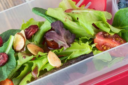bento box: Close up of bento box with fresh homemade green salad with raspberry walnut dressing.