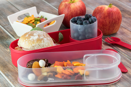 bento box: Close up of bento box with ham cheese sandwich, apples, cup with blueberries, trail mix snack.