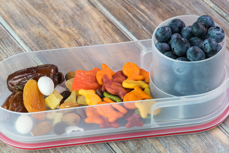 Close up of bento box with trail mix snack and cup with blueberries
